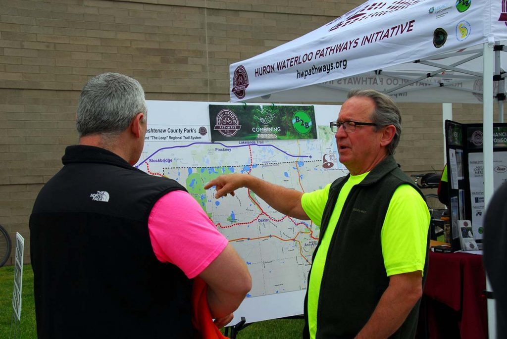 HWPI board member Greg Peter describes the planned regional trail system to a booth visitor at an event in Chelsea. Photo by Rob Mahan.