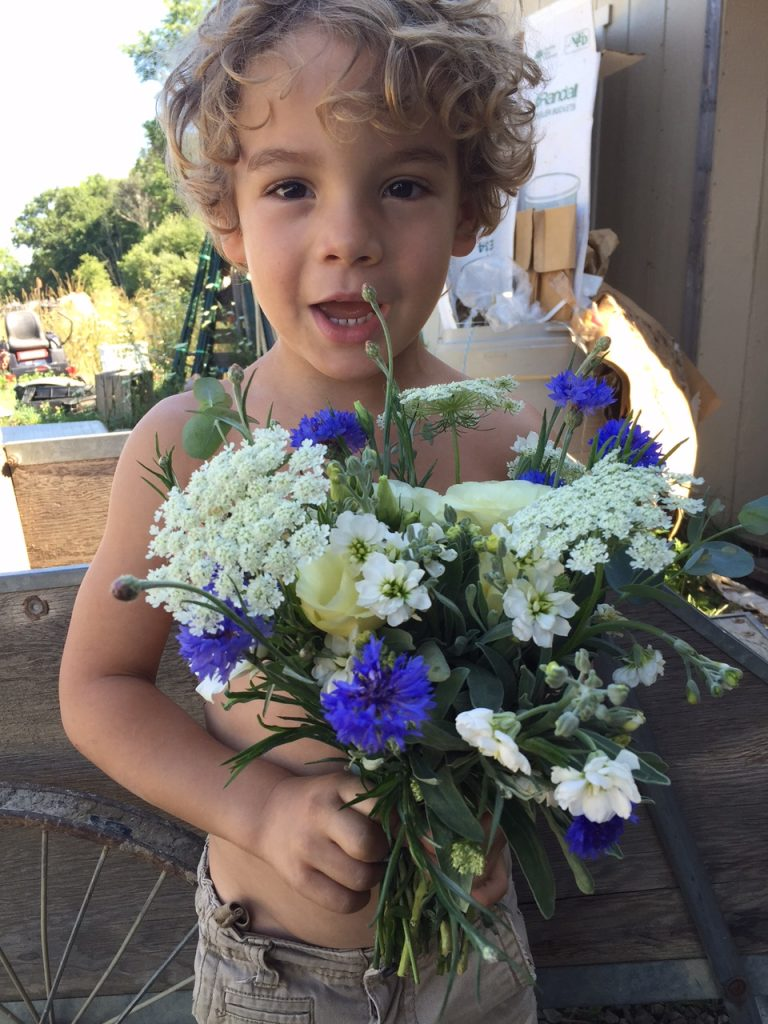 Silas, age 4, helps his mom model a beautiful bouquet. Photo by Trilby Becker.