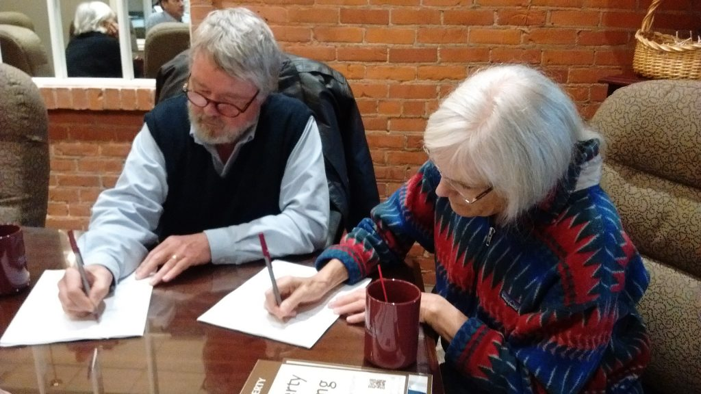 Dave Foster and Cathy Kamil sign the documents that protect their land. Photo by Remy Long.